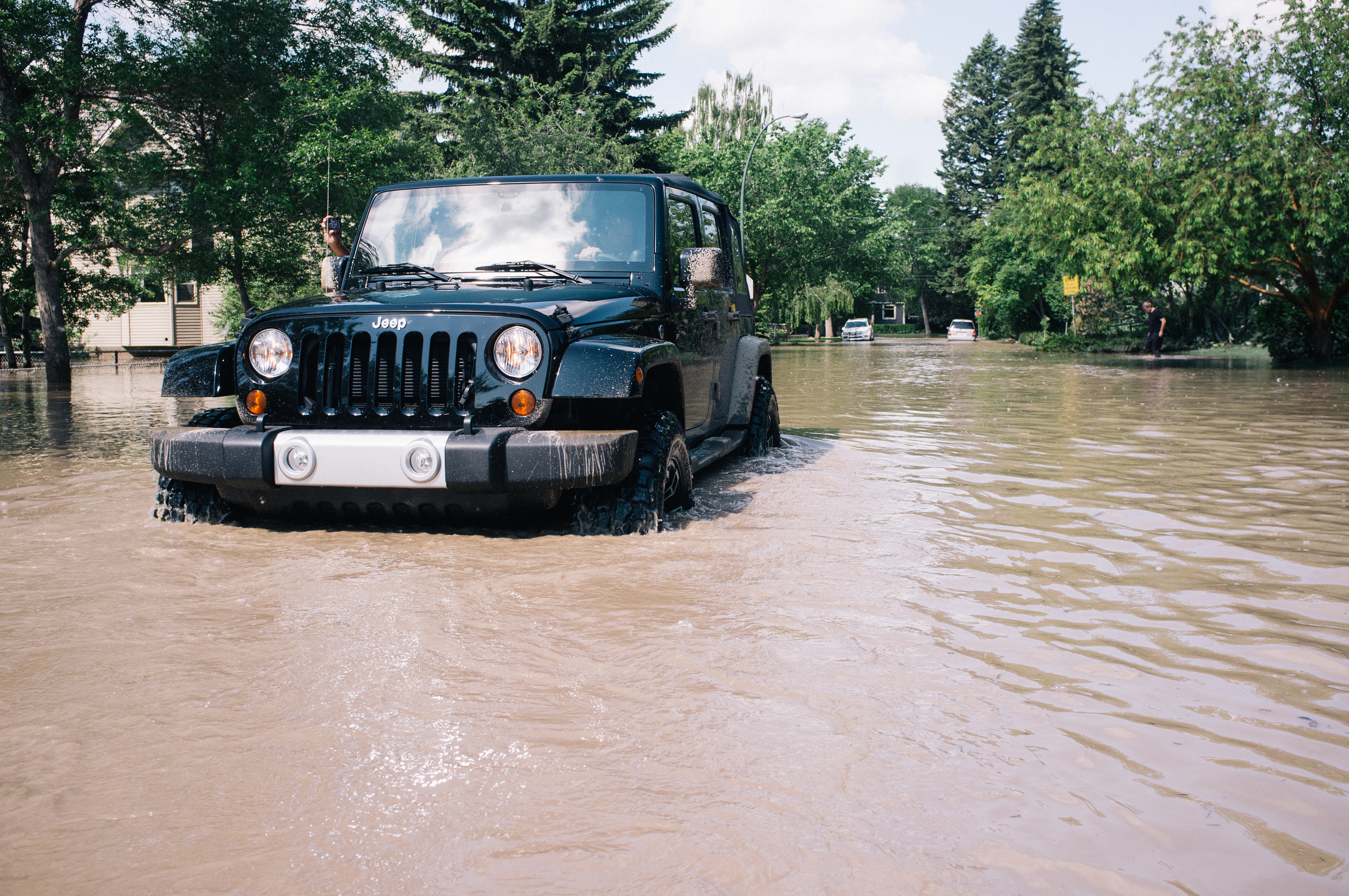 A driver retreats from waist-high waters. I had a heartbreaking conversation with a homeowner that had just returned moments before this. The waters having receded about 2', much of the playground to my left lie completely submerged. I wasn't comfortable travelling further east up this street.