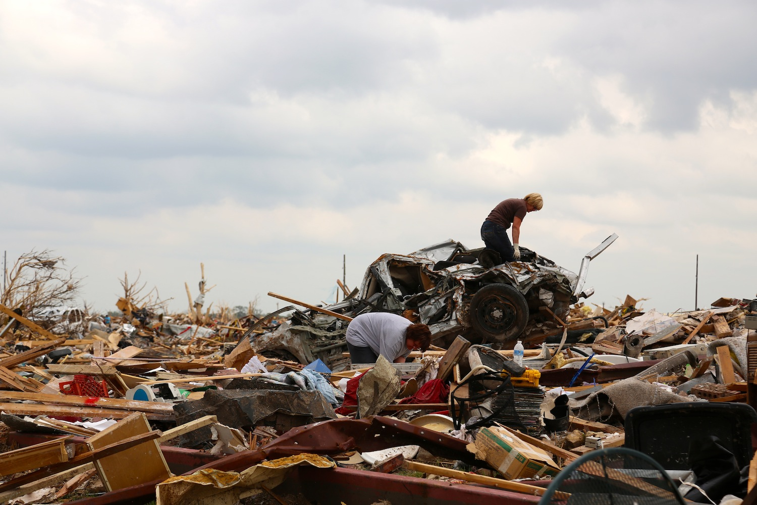Kim Schwab of Oklahoma City (standing on the car), looks for a rosary among the rubble of her home.
