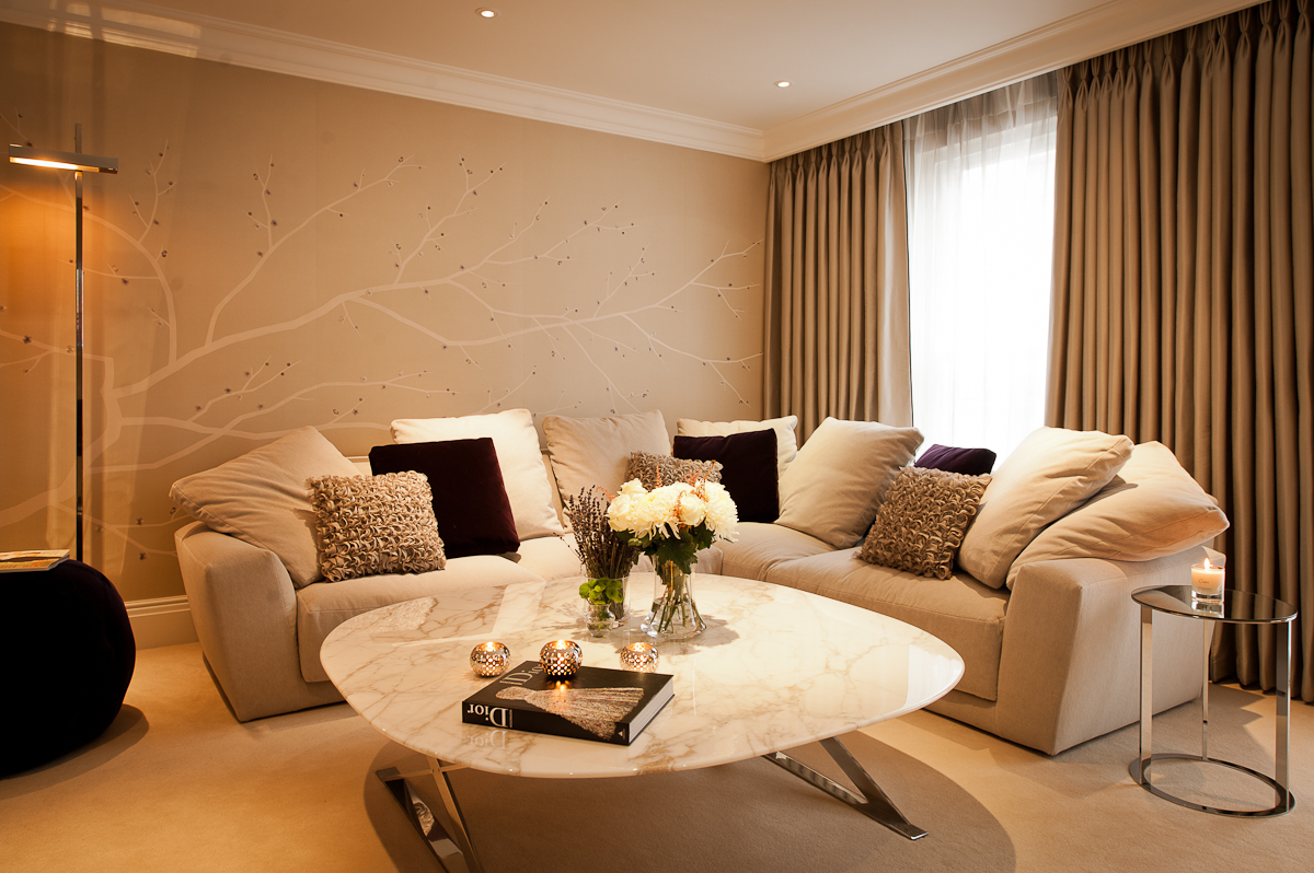 The hand painted and embroidered silk wallpaper acts as a calm and elegant backdrop to the living room.