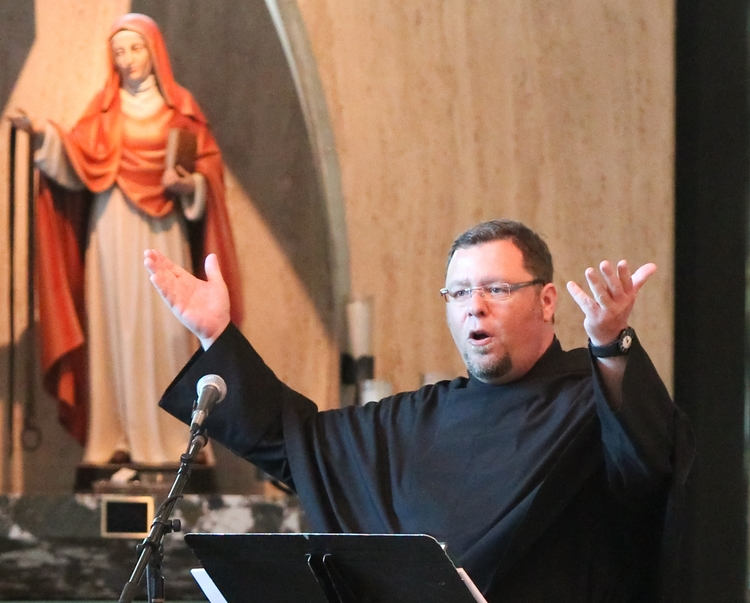 Fr. Rich Young, O.S.A. leads music at St. Rita of Cascia High School, Chicago, near a statue of St. Monica