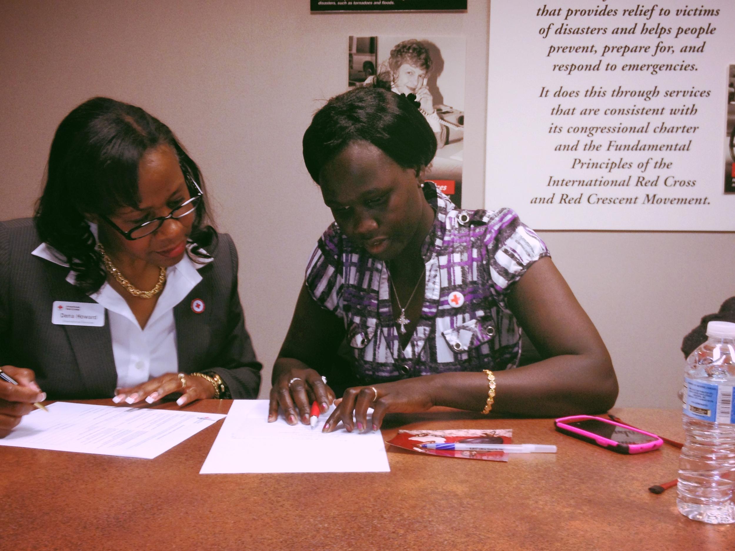 Rhoda Naylera Gatlek (right) works with American Red Cross caseworker, Dena Howard (left).