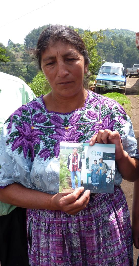 Guatemalan mother holding a photo of her son who has been missing since 2010