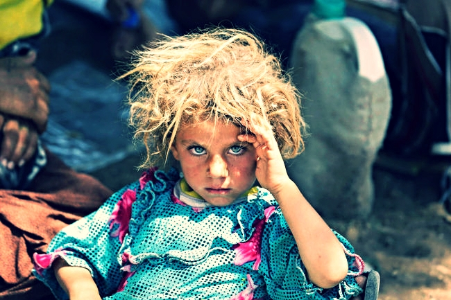 A girl from the minority Yazidi sect, fleeing the violence in the Iraqi town of Sinjar, rests at the Iraqi-Syrian border crossing in Fishkhabour, Dohuk province, Aug. 13, 2014. Credit: Youssef Boudlal/Reuters