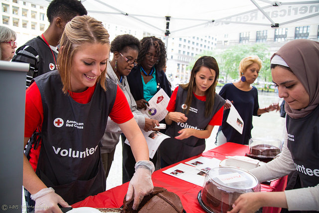 Red Cross volunteers pass out cake to celebrate World Refugee Day and the 100th anniversary of the Red Cross Greater Chicago Chapter.