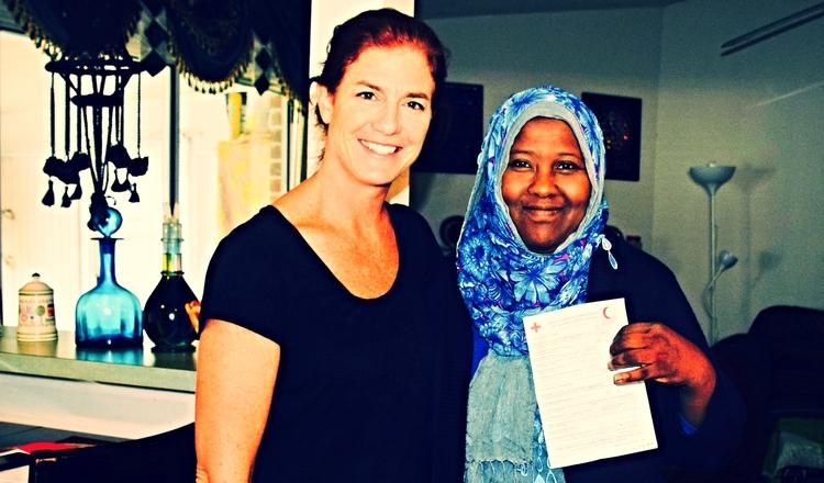 Photo: Amber Bierfreund/Cruz Roja Americana. Khadra Farah hace una pausa para tomar una fotografía con su trabajadora de caso, Liz Smith, después de leer el mensaje de la Cruz Roja mandado por su hermana desde Yemen.