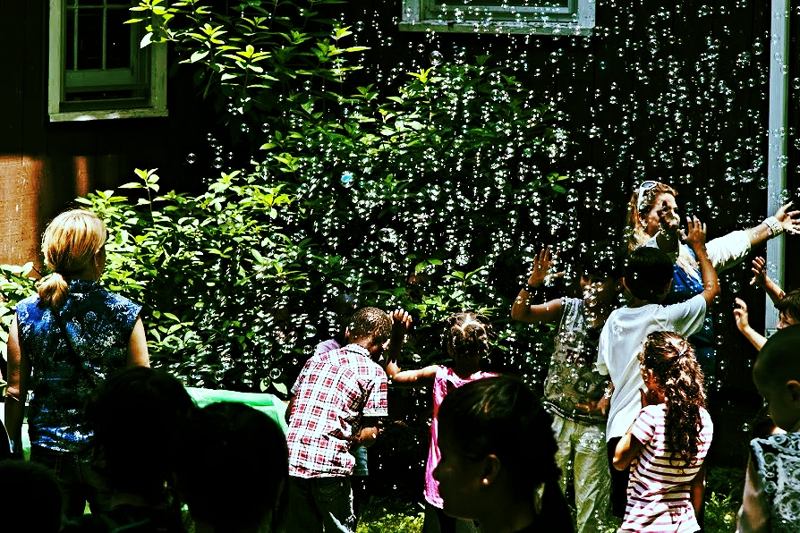 Children play in bubbles during the water festival at World Refugee Day.