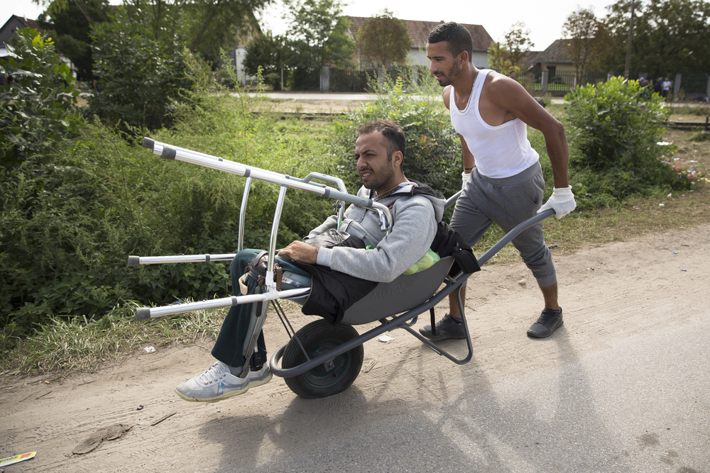 Massur Nasser pushes his friend,Gazi El Fadour, in a wheelbarrow with a flat tire in Horgos, Serbia.El Fadour lost both his legs when ISIS attacked his university in Aleppo. The two men have been traveling companions since meeting months earlier in Turkey. Credit:  Jodi Hilton