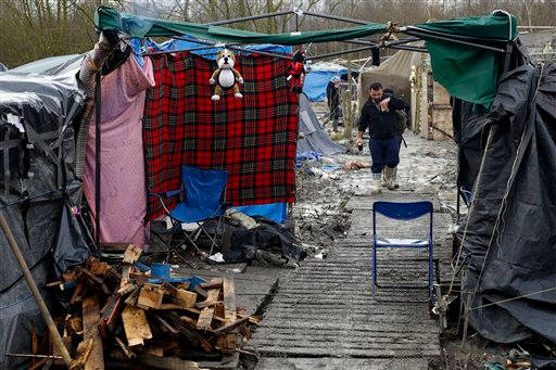 Migrants walk in the mud in a makeshift camp where over 1,000 migrants mostly from Iraqi Kurdistan live in Grand-Synthe, near the northern town of Dunkerque, France, Wednesday Feb. 24, 2016. Photo Credit: Jerome Delay/AP