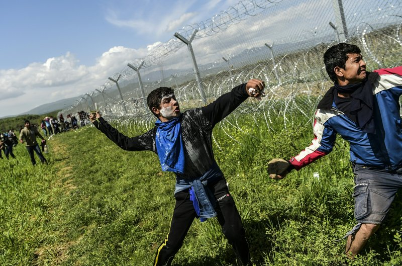 Refugees and migrants clash with Macedonian soldiers as they storm the border fence near Idomeni on Sunday. Bulent Kilic/AFP/Getty Images