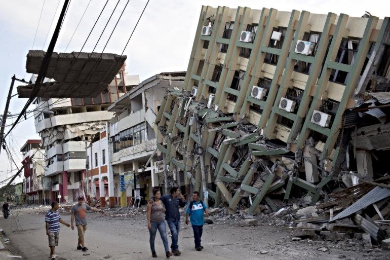 Residents walk Monday past a row of buildings felled by Saturday night's 7.8-magnitude earthquake in Portoviejo, Ecuador. Photo credit: Rodrigo Abd,Associated Press