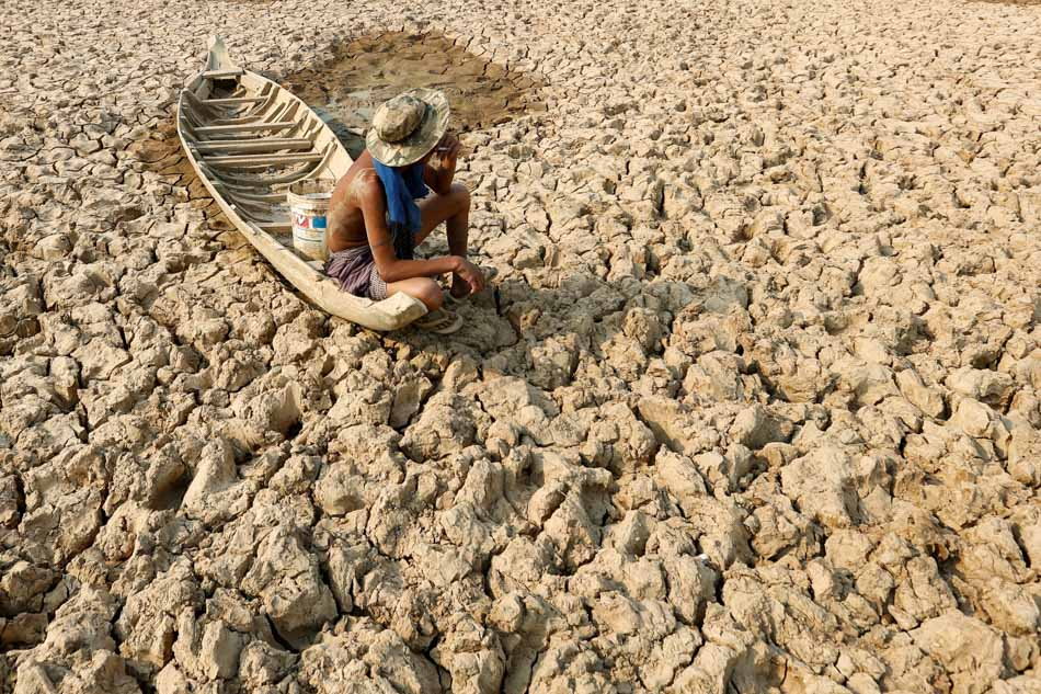 A fisherman sits to smoke on his boat at a Bak Angrout dried-up pond at the drought-hit Kandal province in Cambodia. Southeast Asian countries have experienced rising temperature, which caused heat waves and dry spell as El Niño weakens in the region. Photo credit: Samrang Pring, Reuters. .