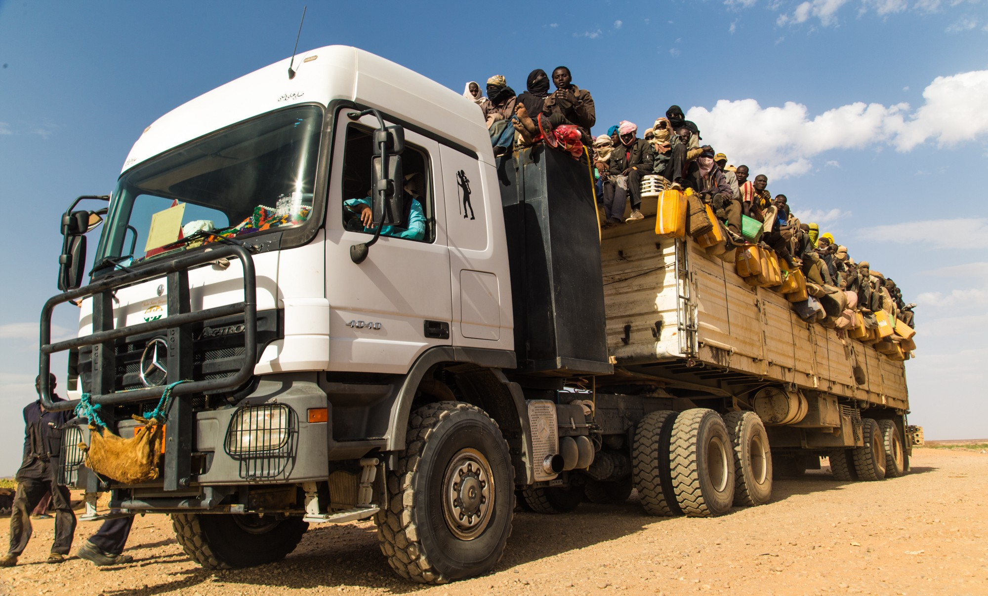 Packed into a lorry, searching for a better life. Photo Credit: ICRC