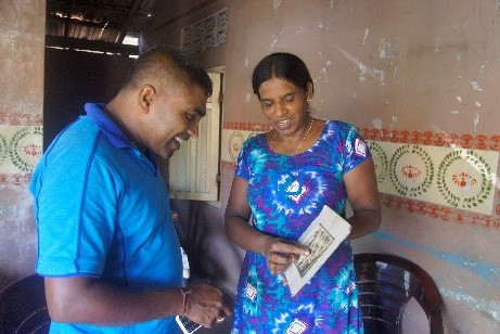 Nesan's wife shares a family photo with Ravi Kumar at their home in Mannar. Photo Credit:Pascal Jequier/ICRC.