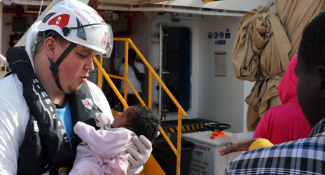 Michael Kühnel-Rouchouze receives an infant from a rubber boat that carried a total of 170 people, men, women and children. Thorir Gudmundsson/IFRC