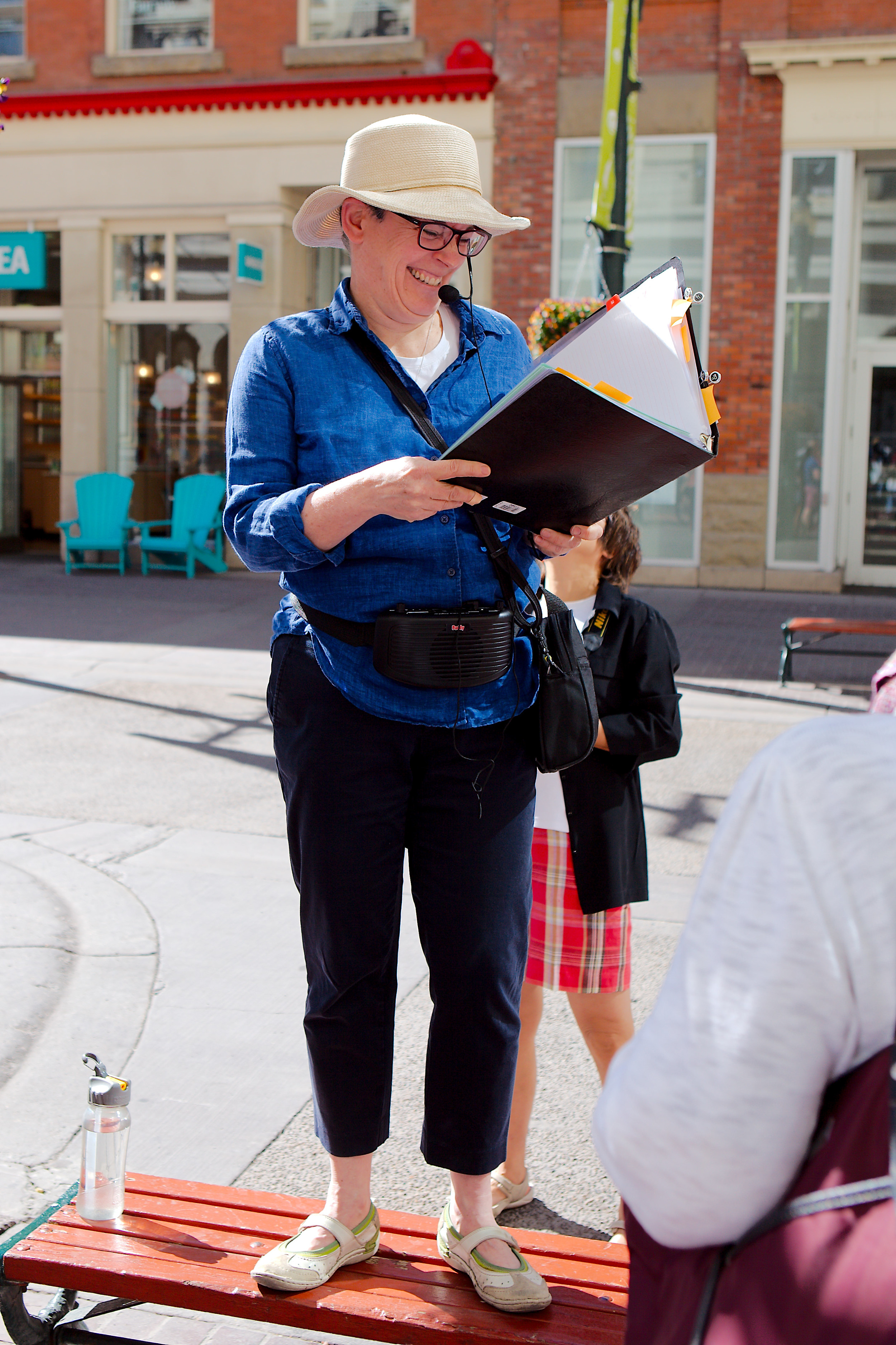 Life is good when you get to wear a headset, stand on a bench and tell Calgary stories in the sun. (Photo: Reg Tiangha)