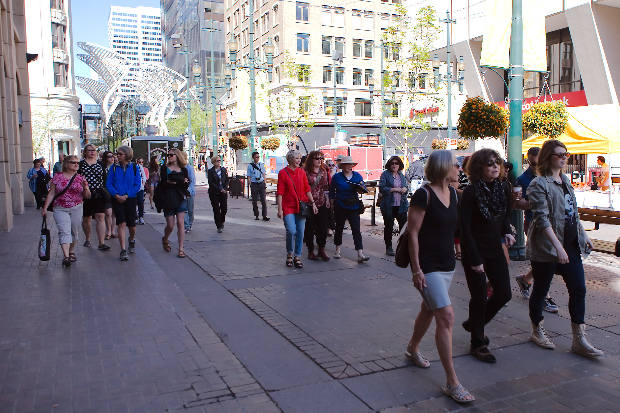 Stephen Avenue: A Jane's Walk parade down what was the 1912 Stampede parade route. Novelist Nancy Huston ( Plainsong ) and poet Yvonne Trainer ( Tom Three Persons ) capture two different aspects of Guy Weadick's first Stampede. (Photo: Reg Tiangha)