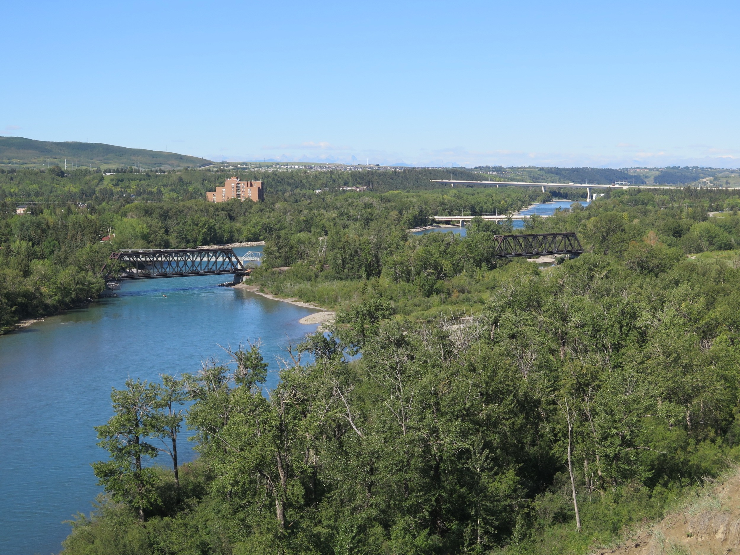 The landmark twin railway bridges in Bowness, looking west from Bowmont Park, with Stoney Trail in the distance (Photo: Blair Carbert)