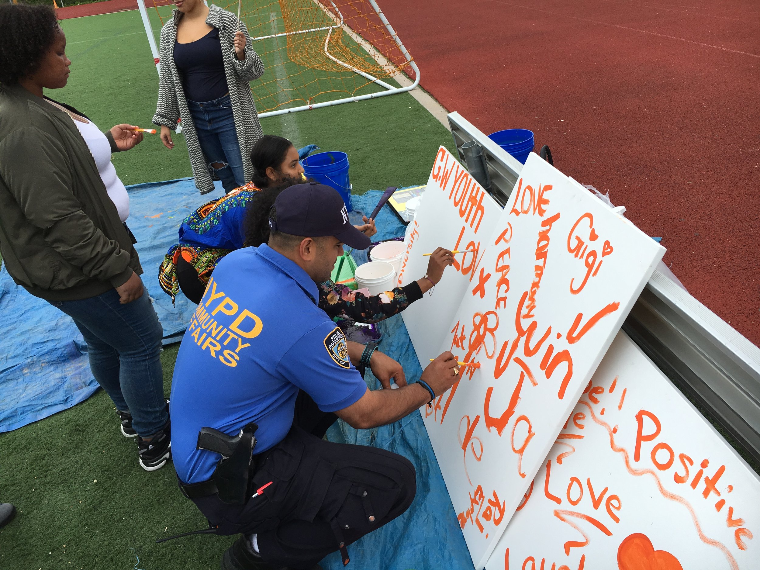 Artist Jamilex Tavares oversees as NYPD, Community members and Youth paint together.