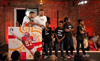 """Travis Kelce started Eighty-Seven & Running because of what he saw during his childhood. Growing up in the diverse suburb of Cleveland Heights, Ohio, his community transcended normal economic and cultural boundaries; merging rich and poor, black and white, and different religious affiliations into one big melting pot. Because of this he noticed some of his closest friends didn't have the same family structure he was blessed with, and weren't able to enjoy the same experiences.  While he was supported by """"the village"""" of family and individuals in the community, Kelce struggled in school and at times lacked the motivation to keep going. Many of the people he considered role models in the community never came back to support their hometown once they reached success. Because of these experiences, Kelce felt obligated to provide opportunities to disadvantaged youth and to help them aspire beyond their current situations. Now as tight end #87 for the Kansas City Chiefs, Kelce's passion for changing the plight of youth experiencing adversity is the inspiration behind Eighty-Seven & Running.  Eighty-Seven & Running helps underserved youth strive to become productive citizens by mentoring and motivating them to explore and develop their abilities while learning critical life skills. Founded in 2015, we have remained dedicated to providing resources and enrichment opportunities for youth and their communities through fundraising, athletic programs, mentoring, and outreach initiatives."""