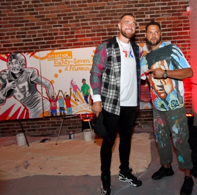 """Travis Kelce and Kyle Holbrook in front of the live mural keystone auction item at """"Walk the Walk Fashion Show"""""""