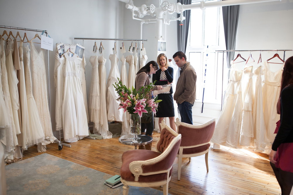 A designer talking to a couple about her collection.