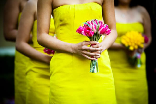 bridesmaids wear neon yellow dresses and carry bright pink tulips