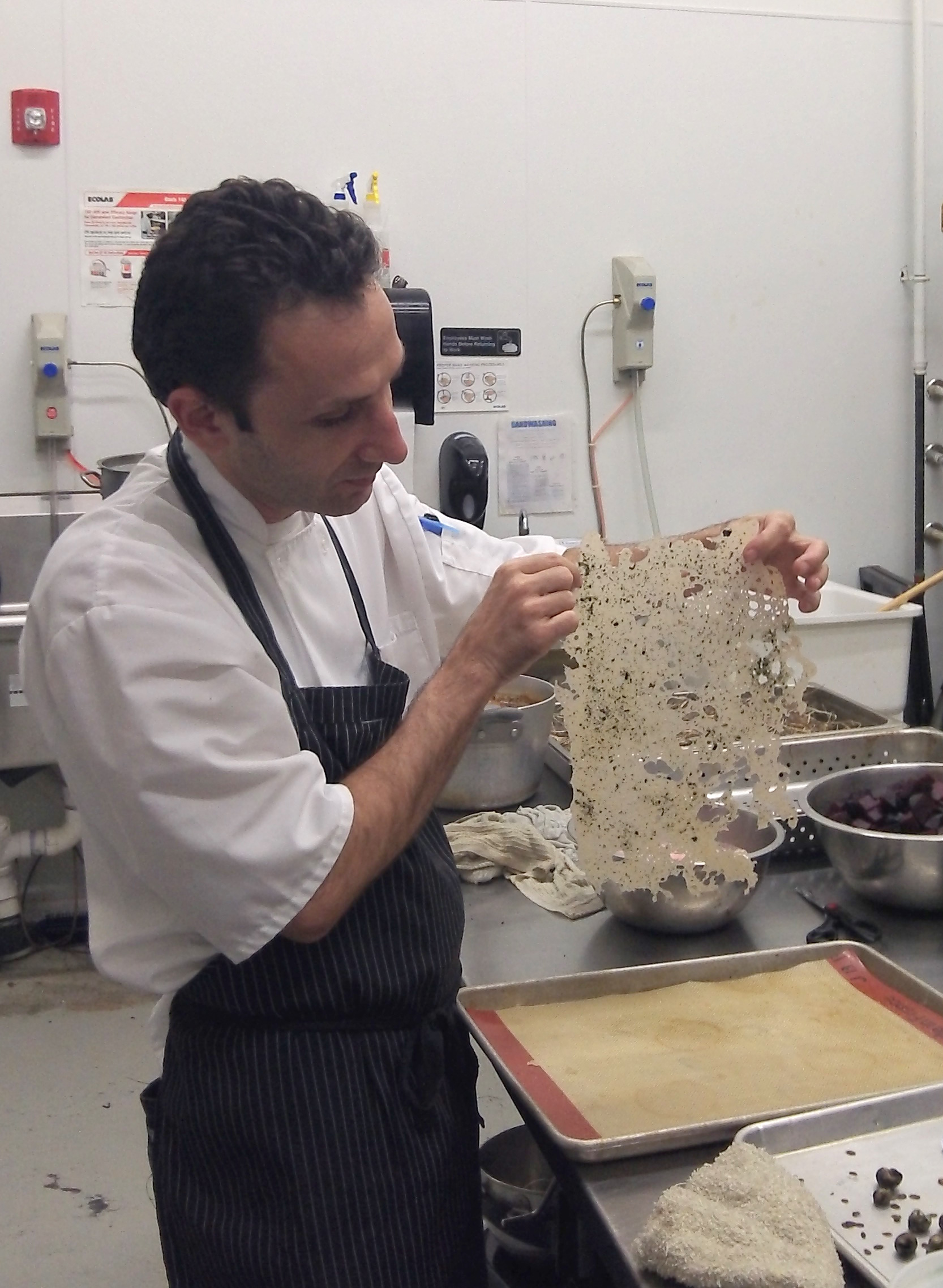 Chef Riz holds up a nori tuille for the cake