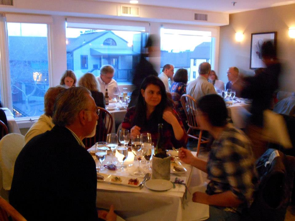 Guests enjoy the shellfish trio, with sunset occurring outside.
