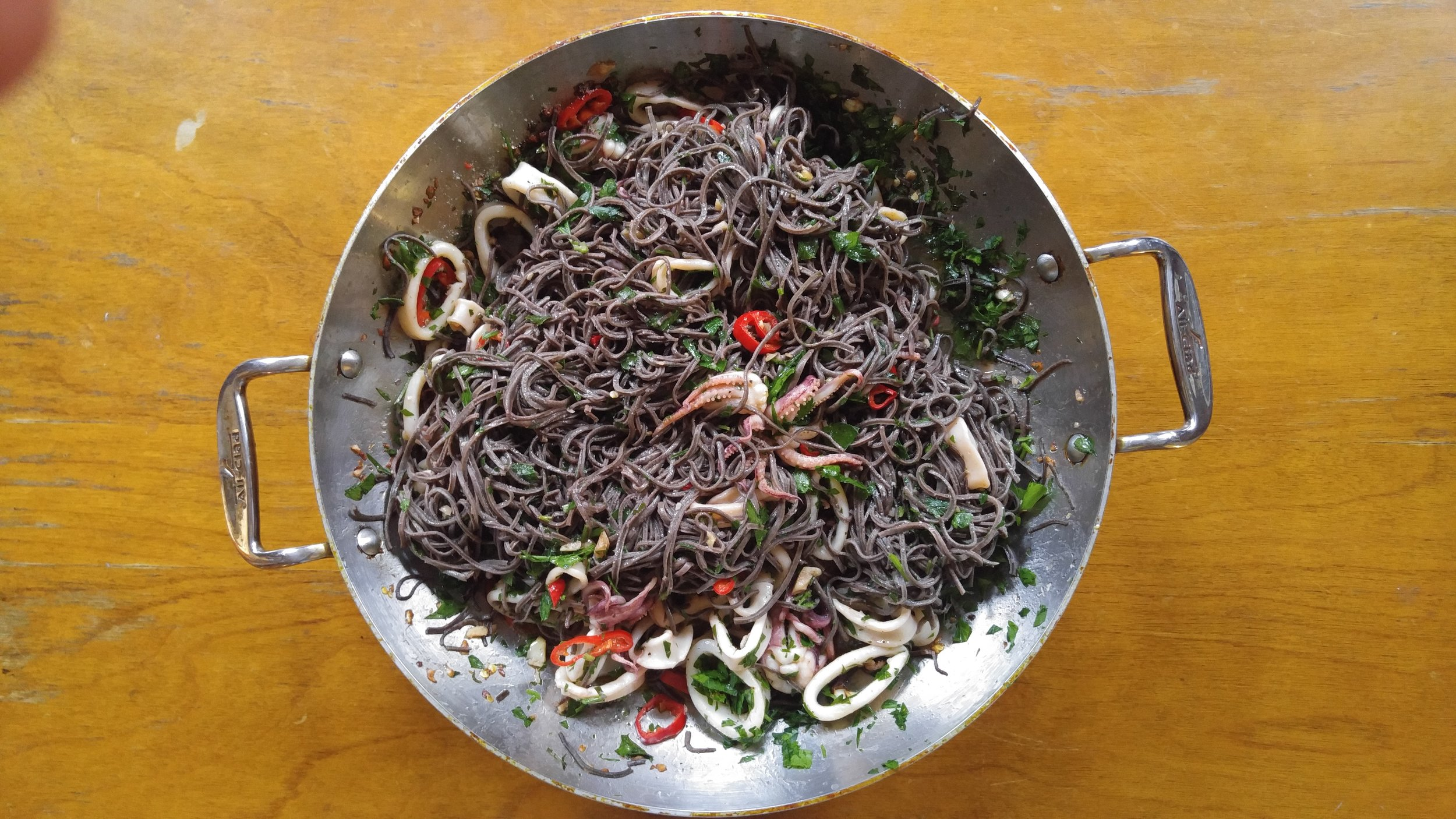 Squid over black bean pasta with jalapenos, parsley and garlic