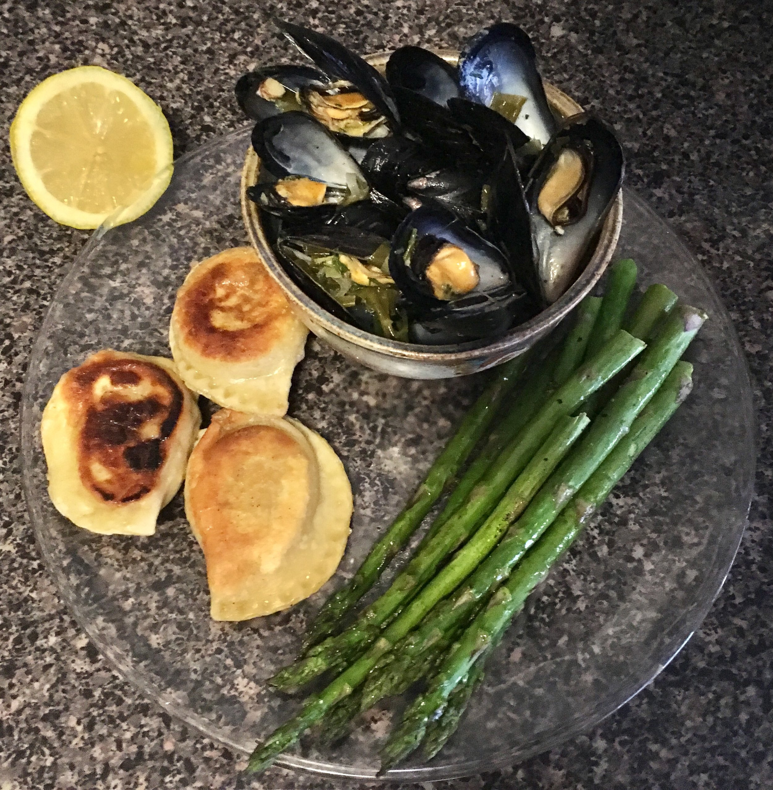 Mussels cooked in a garlic scape and dill white sauce with perogies and asparagus