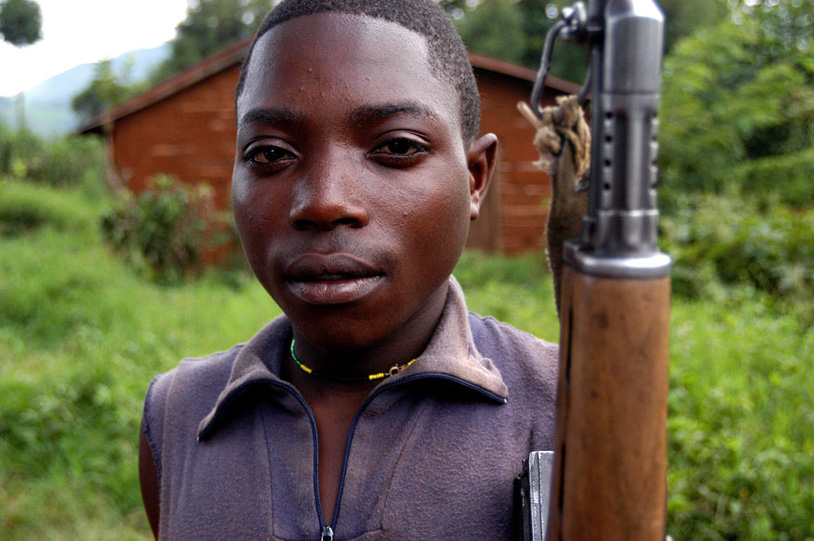 Ombeni Balihiamwabo, 17, stands with his rifle Thursday Dec. 9, 2004, outside a military post in Nyangonbe, in the Democratic Republic of Congo. The integration of the former militias in the new Congolese army is a priority task for the transitional government. Photo: Riccardo Gangale.