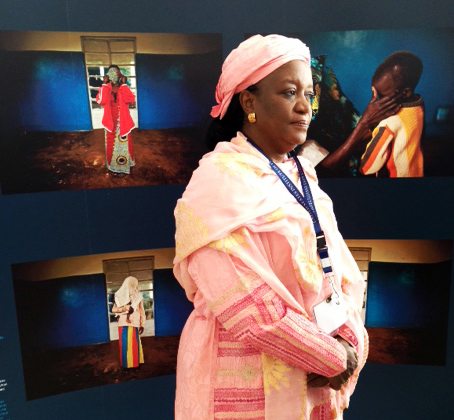 "Ms Zainab Bangura,  Special  Representive to the  UN  for Sexual Violence in Conflict, who participated in The Missing Peace  Symposium, February 12-16, 2013, at the United States  Institute of Peace, Washington D.C, stands in front of ""The Legacy of Rape"" exhibit's DRC panel."