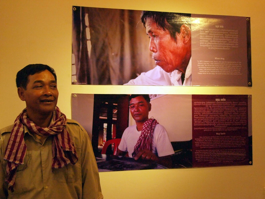 Cambodia rescuer Huy Sarin stands next to his story and photograph at The Rescuers exhibit in Cambodia, November 2011. Photo: Willhemina Wahlin.