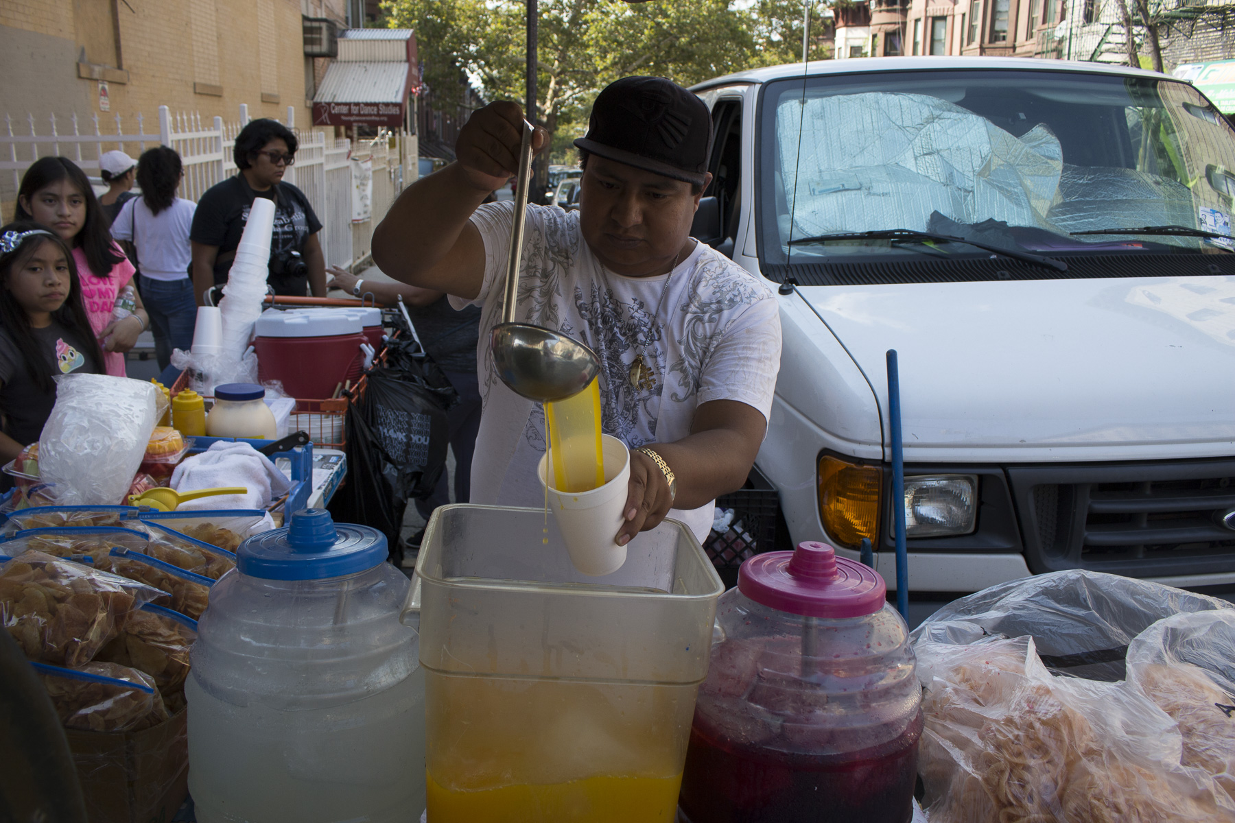 Sergio pouring jugo de mango for eager customers on the 22nd of August, 2017. Sunset Park, Brooklyn