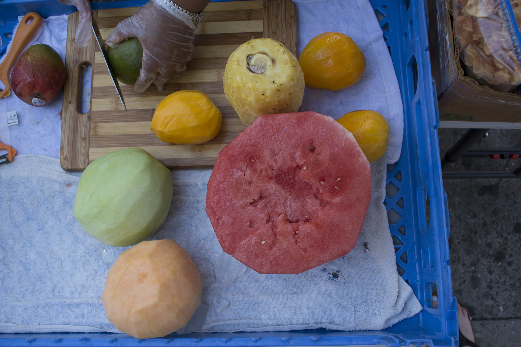 Teodosia is peeling mangoes, honeydew, cantaloupe, pineapple, and watermelon in preparation to cut and pack to sell. She buys her fruit from various places. August 22nd, 2017 Sunset Park, Brooklyn.