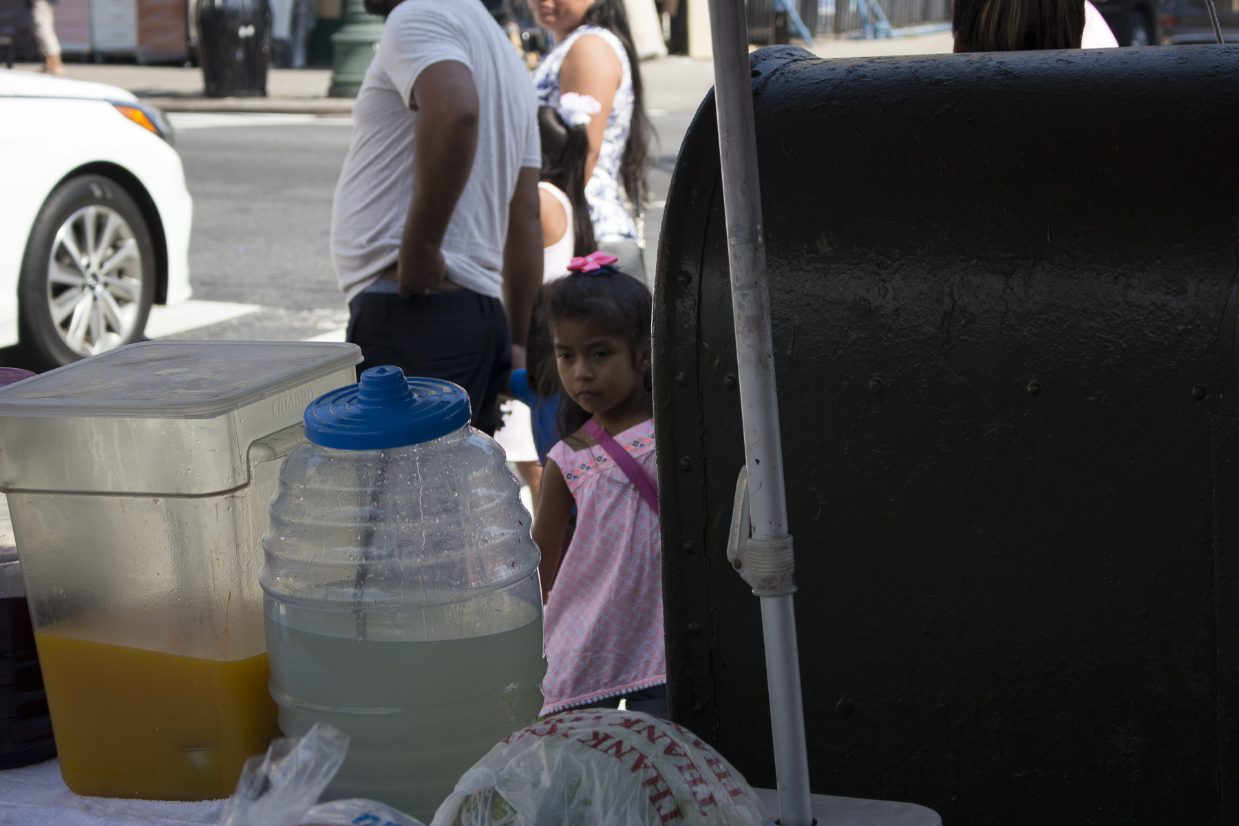 A little girl waiting with her mother to buy products from the fruit stand on the corner of 5th and 56th street. She is gazing at the limonada and jugo de mango that is for sale of August 22nd, 2017.