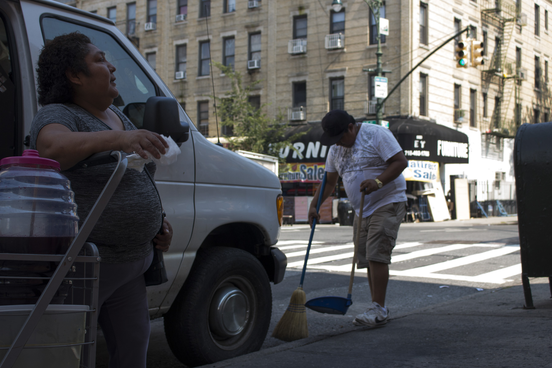 Sergio sweeps the corner of 5th and 56th street everyday before setting up the stand. On August 22, 2017, Teodosia stands there speaking to us and him.