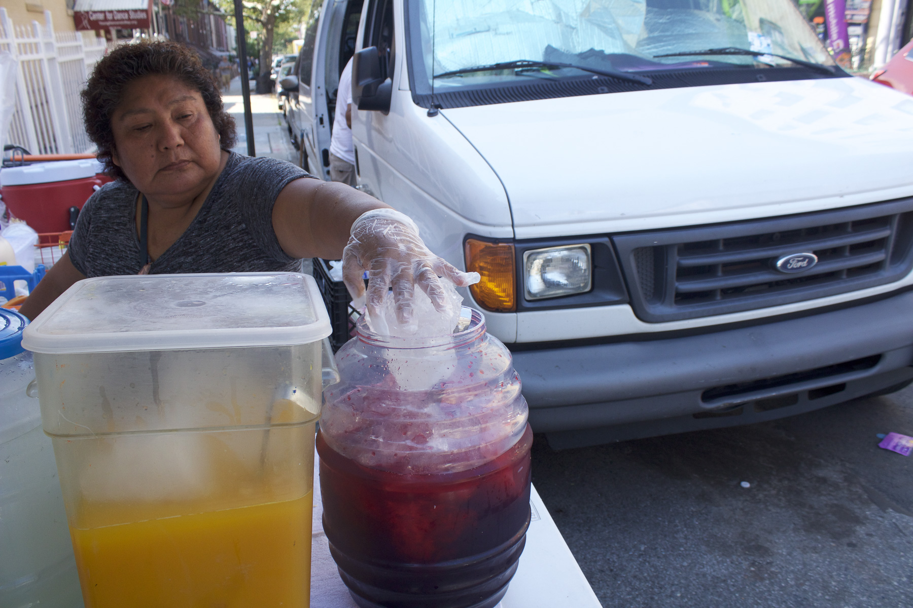 Teodosia putting the chunks of ice she cut into the jamaica on a hot day in Sunset Park, Brooklyn. August 22nd, 2017.
