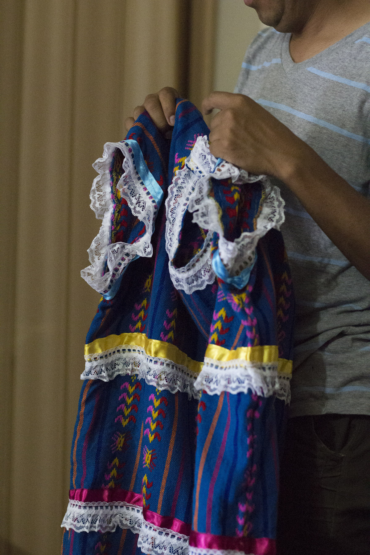 Benito Bravo holds up a costume made by indigenous women in Mexico, noting the stitching and careful attention to detail in the handiwork.  Gabrielle Narcisse and Deleelah Saleh for Picture Justice. August 22, 2017.