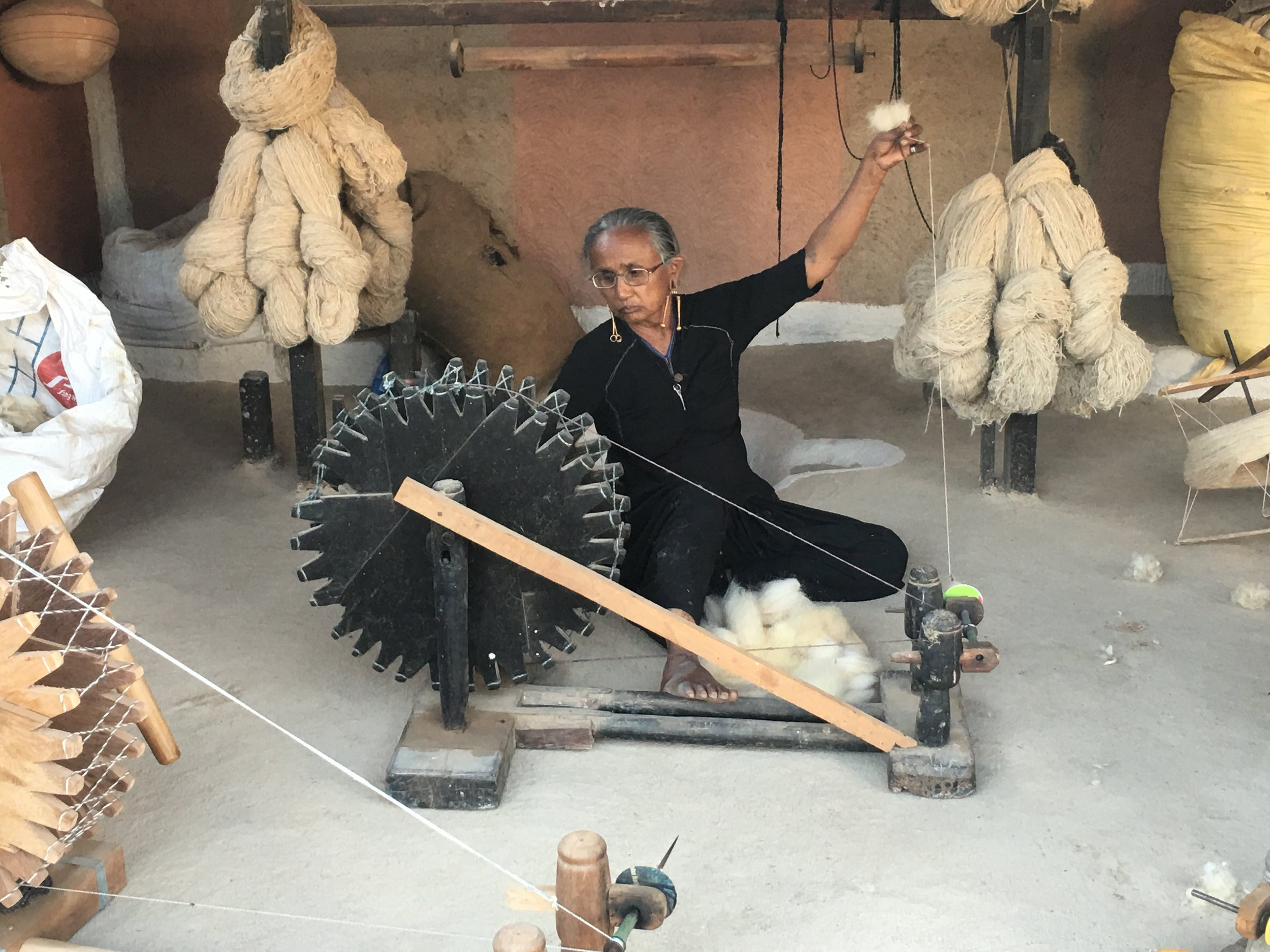 Rabari woman spinning local Desi wool on a traditional spinning wheel called a charkha, in Kutch (Kachchh)