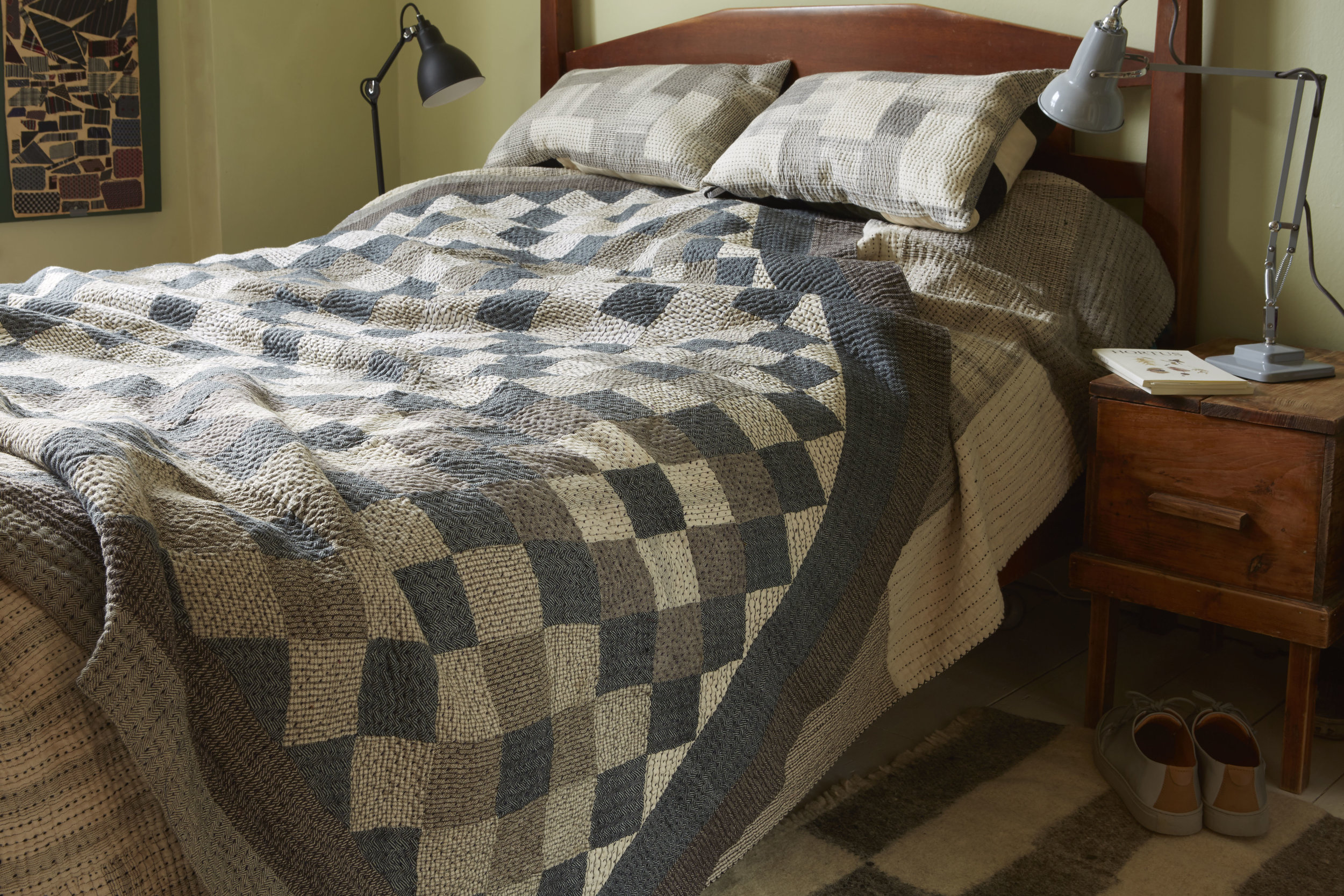 A Stitch by Stitch patchwork Khamir Cubes Quilt in organic kala cotton layered with a Chindi Quilt in one of the bedrooms.