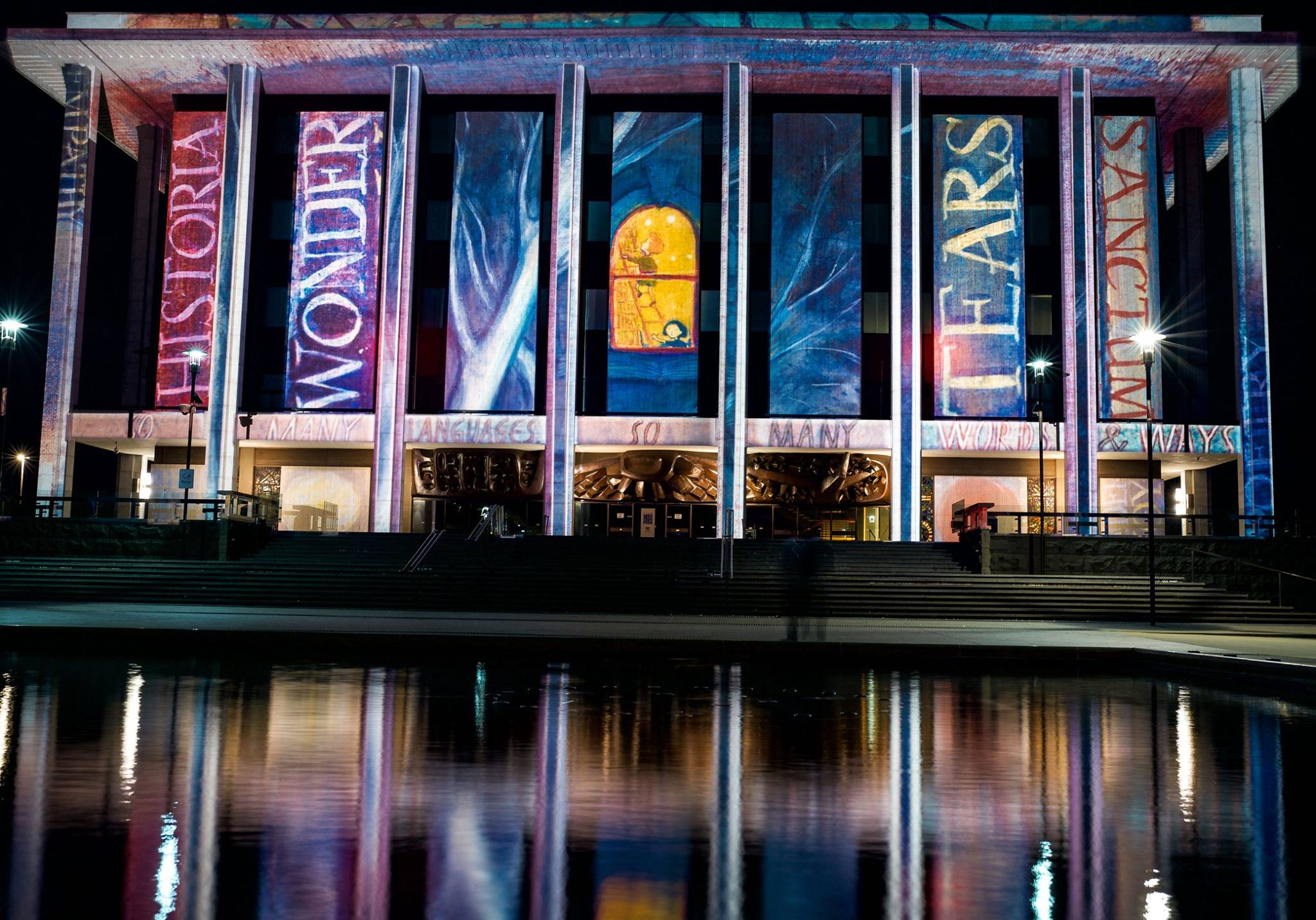 "A projection at the National Library of Australia of ""Midnight at the LIbrary"" by Ursula Dubosarsky, illustrated by Ron Brooks, as part of the Enlighten Festival 2019."