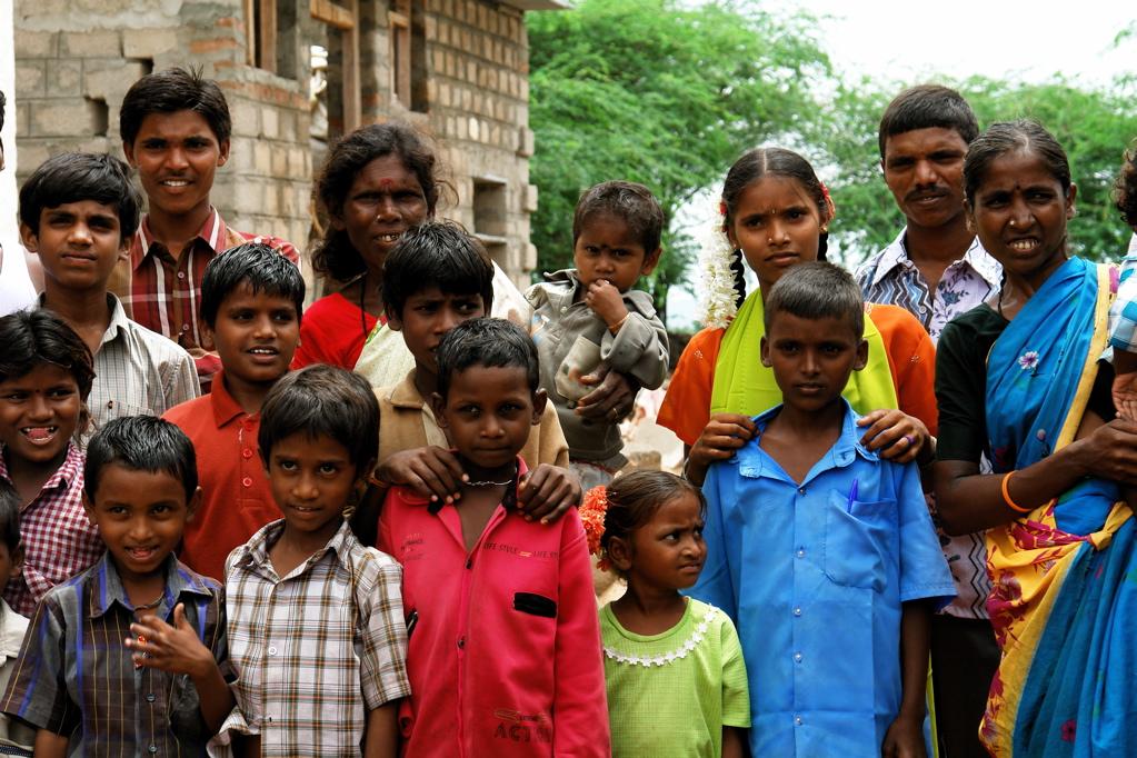 Nagavani, vestida con un punjabi naranja, posando con parte de su familia y vecinos.