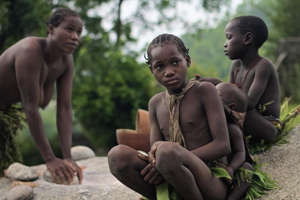 Una niña koma espera a que la madre del niño a quien carga termine de moler el grano de mijo.