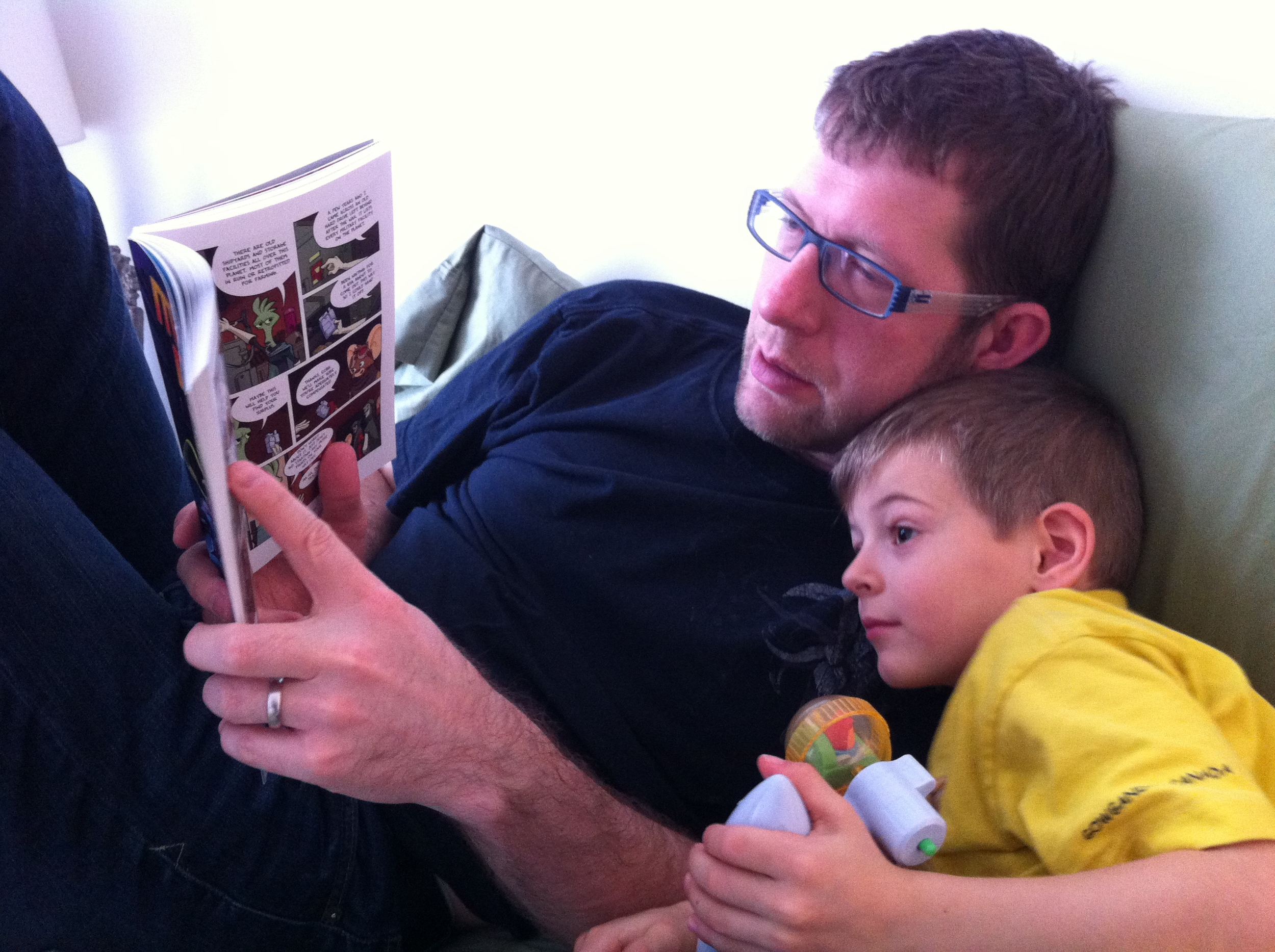 My boys snuggled up and reading Missile Mouse comics.