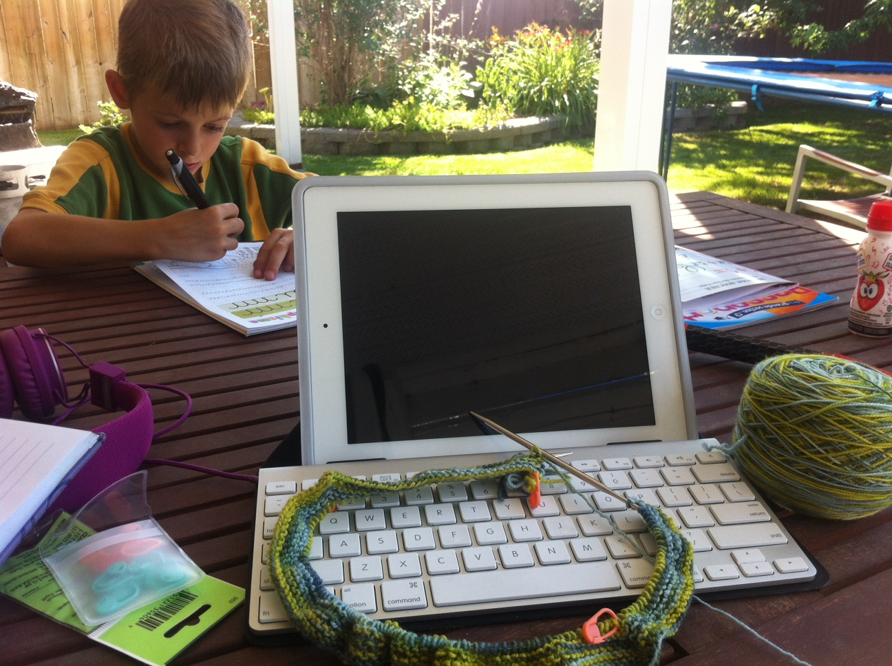 Harrison diligently doing his graphisme while mummy knits, er, looks on.