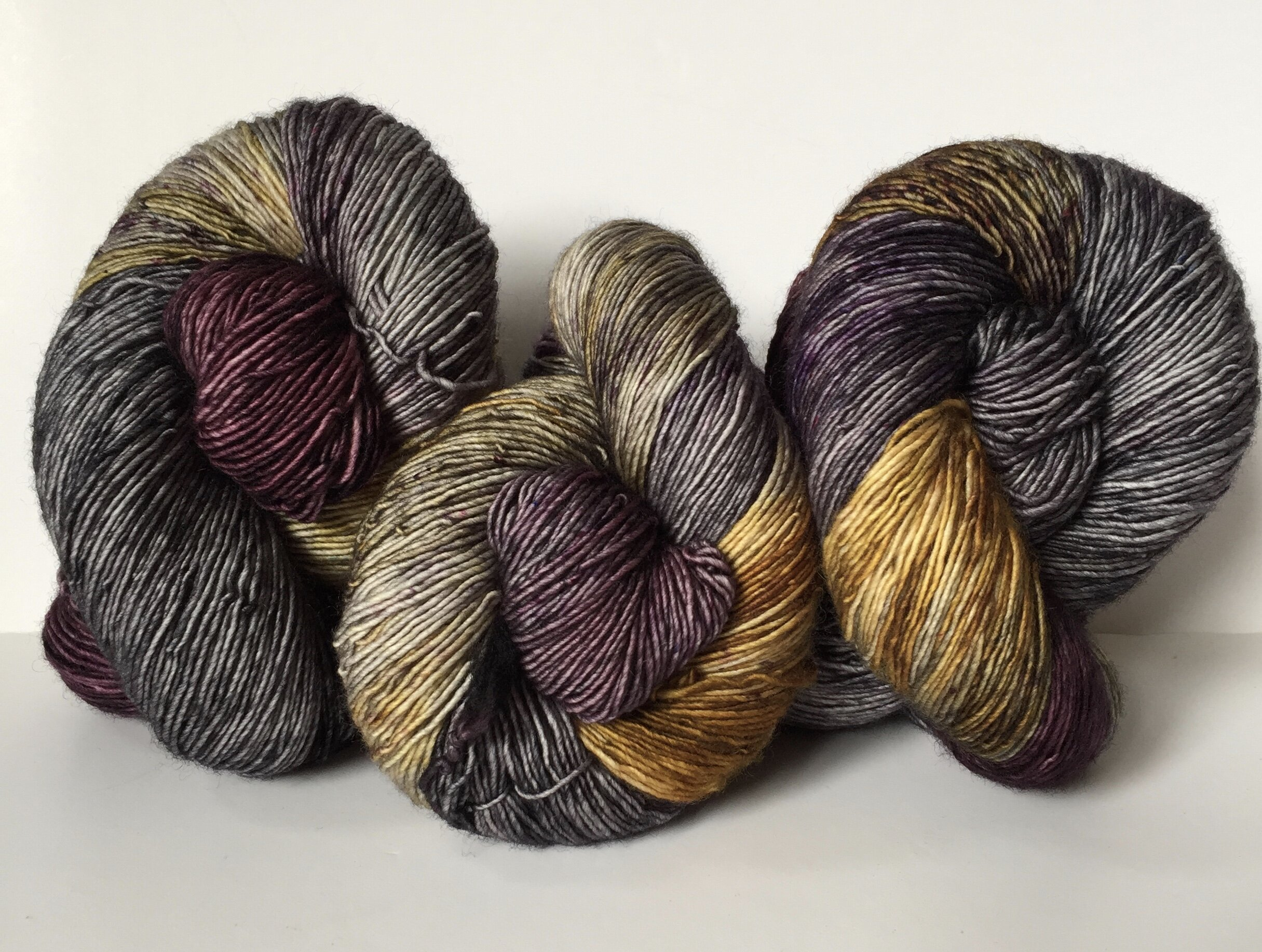 Obsession on Merino Singles, a variegated charcoal, gold and aubergine with speckles