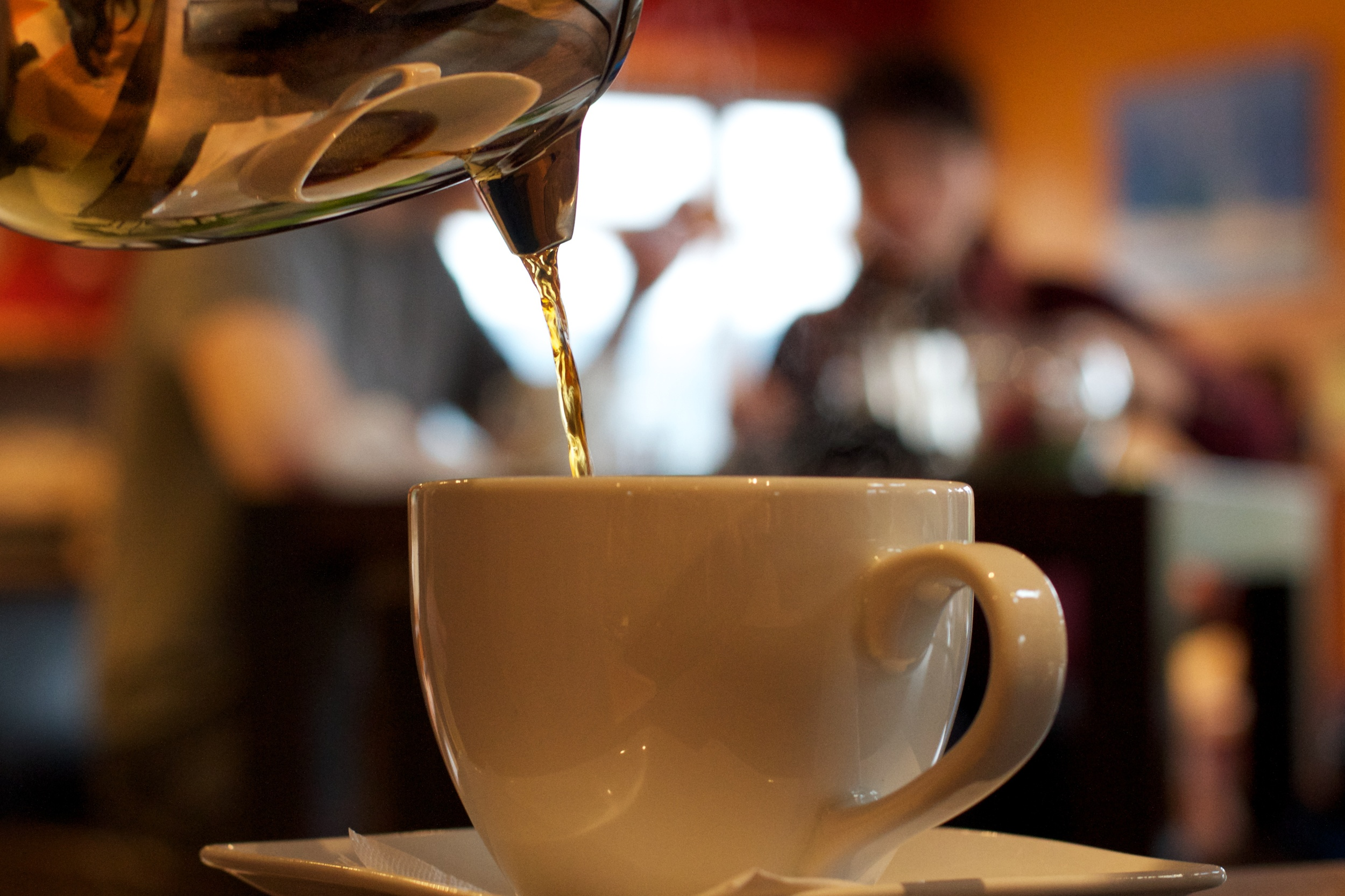 Coffee is poured as friends sit talking in the background.  Canon EOS 7D EF 50mm at f/4 1/60 ISO 1250