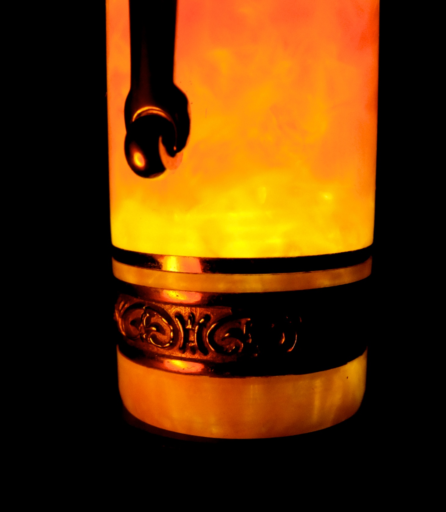 The orange celluloid of a Delta Dolce Vita fountain pen cap glows with an internal fire.  Canon G10 at 7mm f/8 1/60 ISO 800 iPhone light shining through the end cap.