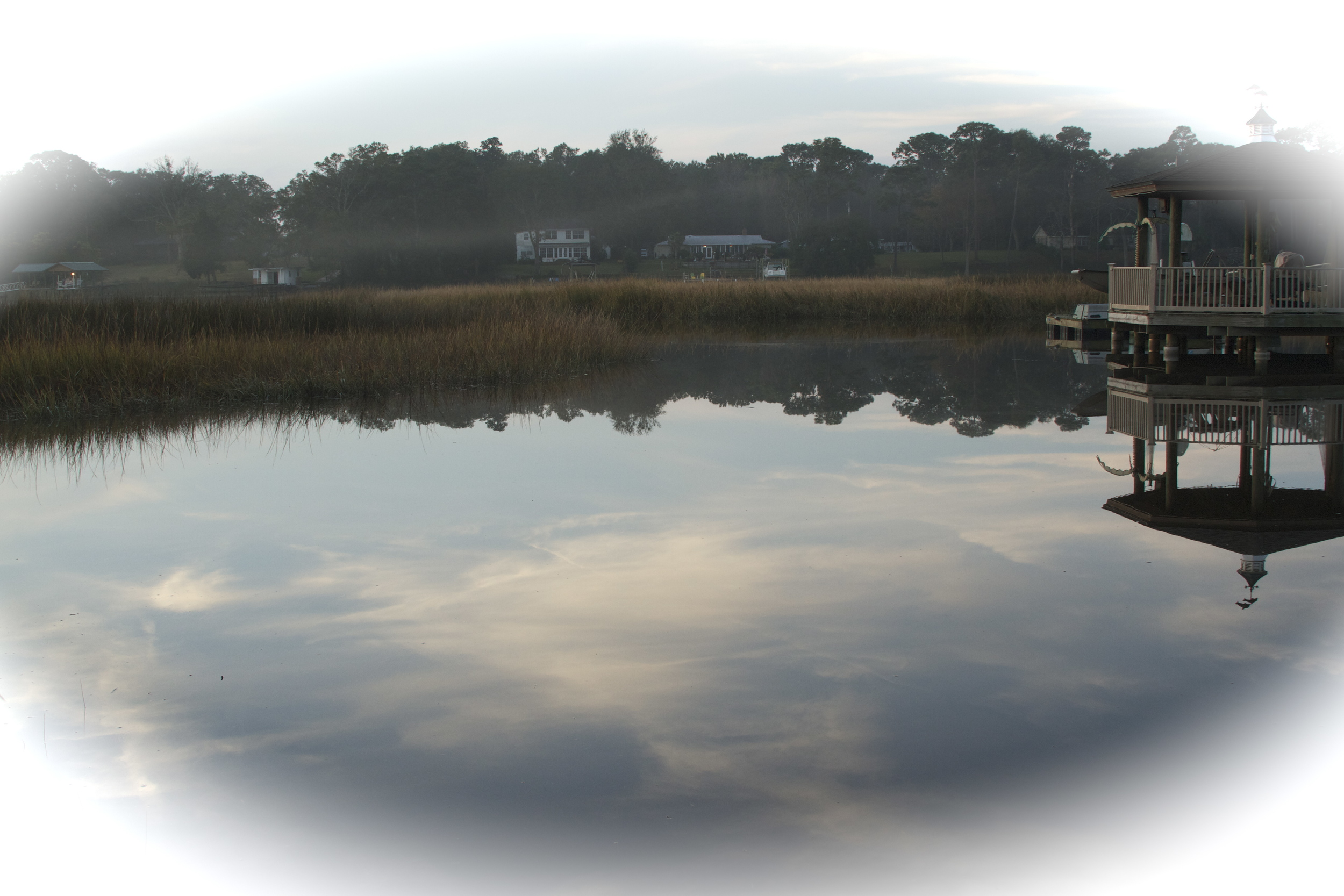 A Wispy mist rises over the marsh while the sky reflects the morning light